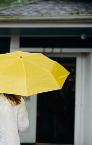 Image of person holding yellow umbrella.