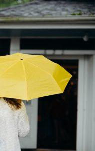 Image of person holding yellow umbrella.